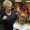 Linda Colton of Hot Springs, left, styles the hair of her granddaughter, third-grade student Kristen...