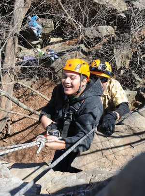 Jonathan Barrientos, a Rogers High School student with cerebral palsy, rappels down a cliff with outdoor education instructor Jeff Belk Dec. 12 at Lincoln Lake. Rappelling and rock climbing are two of many skills students learn in outdoor education at RHS and other area schools.