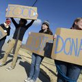 Samantha Farley, from left, 16, Keaton Duersch, 16, Katie Wilson, 17, and Emma Hackett, 17, wave sig...
