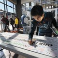 "Willy Butihi, a junior at Heritage High School, signs a banner that reads ""Our Thoughts Are With You..."