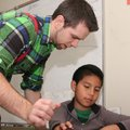 Kyle Queen, fourth-grade teacher at Bonnie Grimes Elementary School, helps Allan Alfaro with compute...