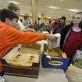 Matthew White, 10, (above left) hands Teresa Blackwood a package of rolls Saturday for her food box ...