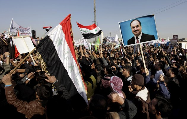 protesters-chant-slogans-against-the-iraqs-shiite-led-government-as-they-wave-national-flags-and-hold-posters-of-the-sunni-finance-minister-rafia-al-issawi-during-a-demonstration-in-fallujah-40-miles-west-of-baghdad-iraq-sunday-dec-12-2012-thousands-of-protesters-have-demonstrated-in-iraqs-western-sunni-heartland-following-the-arrest-of-bodyguards-assigned-to-the-finance-minister-who-draws-support-from-the-area