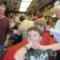 Ryan Howk, foreground, checks out his haircut Saturday after getting trimmed by barber Gary Townzen,...
