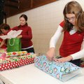 Lily Agnacian, 12, right, secures wrapping paper with a piece of tape Monday while wrapping presents...