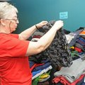 Willa Lawson sorts through hoodies and sweatshirts Monday during the fourth annual Miracle on 14th S...