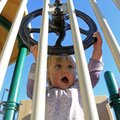 Pilot Miller, 15 months, turns a steering wheel on the playground equipment at Wilson Park in Fayett...