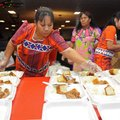 Linda Morris, left, from Marshallese United Church of Christ, adds bread to a tray filled with rice ...