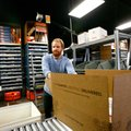Adam Miller sends a CountryOutfitter.com shipment Dec. 7 down the rollers in the warehouse of Acumen...