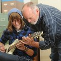 Halen Auxier, an 18-year-old senior at Fayetteville High School, left, gets a hand from guitar instr...