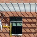 Jose Solano, with CertaPro Painters, paints an overhang Friday, Sept. 28, 2012 on the east side of t...