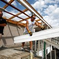 71B Auto Auction employees Shane Wood, and Jared Mitchell toss aside roof and awning pieces from the...
