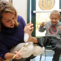 First grader Jack Taylor, 6, right, reacts as his mother, Brooke Taylor, paints the bottom of his fo...