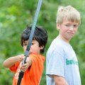 Griffin Roton, 10, right, watches as Keeno Ghadbin, 9, aims his bow and arrow at a target Wednesday,...