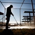 Casey Bridges with City of Bentonville Parks & Recreation pressure washes the seating area for one o...