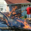 Carson Hanning, 12, sprays the edges of a burn area Saturday, Sept. 22, 2012, while assisting his fa...