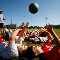 Kyler Cotton, 13, Ethan Cook, 13, both of Rogers, toss a medicine ball during a football sports camp...