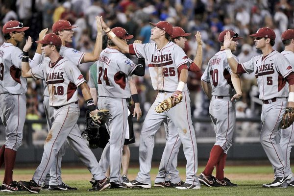 Arkansas players, including Tim Carver (18), Dominic Ficociello (25) and Matt Reynolds (5), exchange high-fives after beating South Carolina 2-1 in an NCAA College World Series baseball game in Omaha, Neb., Monday, June 18, 2012. (AP Photo/Ted Kirk)