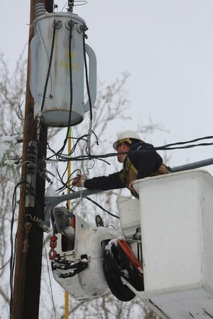 Brandon Wilson, an employee of North Little Rock Electric, reconnects power to homes near West 36th and Gum streets in North Little Rock on Thursday.