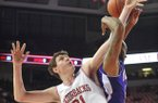University of Arkansas forward Hunter Mickelson and Northwestern State forward DeQuan Hicks fight for a rebound the first half of Saturday night's game. Mickelson and BJ Young both finished with a 13 rebounds, a career high for each player.