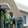 Randy Kaapuni, left, and Jose Zapata, both with Arkansas Glass & Mirror, install sun shades Friday o...