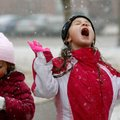 Addyson Ogle, 6, and her sister, Amaya Ogle, 4, try to catch snowflakes Friday outside their home in...
