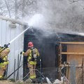 Springdale firefighters douse hot spots Friday during a shed fire behind a home on South Scott Hollo...