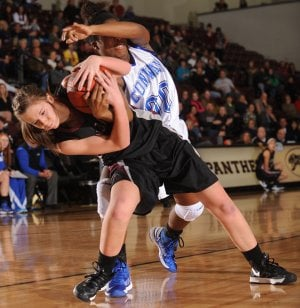 Morgan Miller, left, Siloam Springs junior, and Conway's Asia Willard vie for a loose ball Saturday during the first half of the championship game of the Siloam Springs Holiday Tournament.