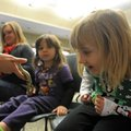 Snake enthusiast Lily Ginn, 4, right, observes the tail of a speckled kingsnake held by Rachel Diers...