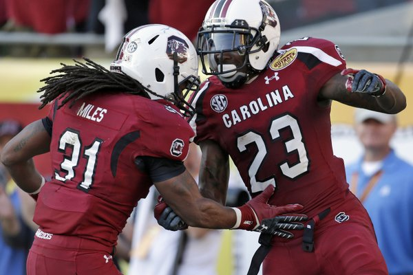 South Carolina wide receiver Bruce Ellington (23) celebrates with teammate Kenny Miles (31) after scoring on a 32-yard touchdown reception during the second half of the Outback Bowl NCAA college football game against Michigan, Tuesday, Jan. 1, 2013, in Tampa, Fla. South Carolina won 33-28. (AP Photo/Chris O'Meara)