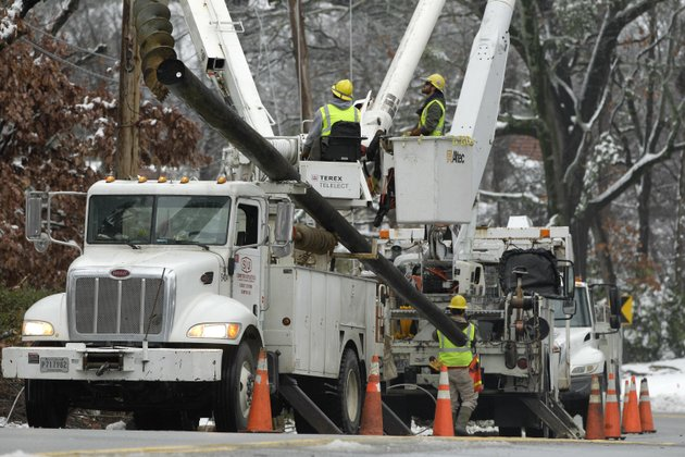 a-utility-crew-works-on-damaged-power-lines-in-little-rock-ark-friday-dec-28-2012-in-the-wake-of-a-christmas-day-winter-storm-leaving-thousands-without-electric-power-officials-with-the-city-are-saying-that-crews-will-be-making-multiple-rounds-in-every-ward-to-pick-up-all-the-debris-left-from-the-storm