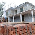 Workers remodel a house Friday at Southwest C and Southwest Fourth streets in Bentonville.