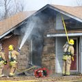 Springdale firefighters hose down the roof of a house at 1305 Daline St. in Springdale Wednesday, Ja...