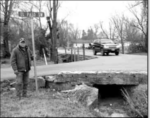 Tim DeWitt, Street and Utililties Director for the City of Gravette, stands at the intersection in Gravette where work will begin soon to help correct a storm water drainage problem.