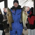 Andy Benson shows a smallmouth bass, left, and largemouth bass from the tournament's winning catch. ...