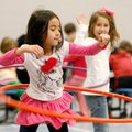 Myra Bui, left, 6, and Kadence Janney, 7, both of Rogers, hula-hoop inside the gymnasium Wednesday a...