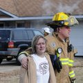 Mike Pellegrino, right, a Springdale firefighter, escorts a girl to an ambulance Wednesday while cre...