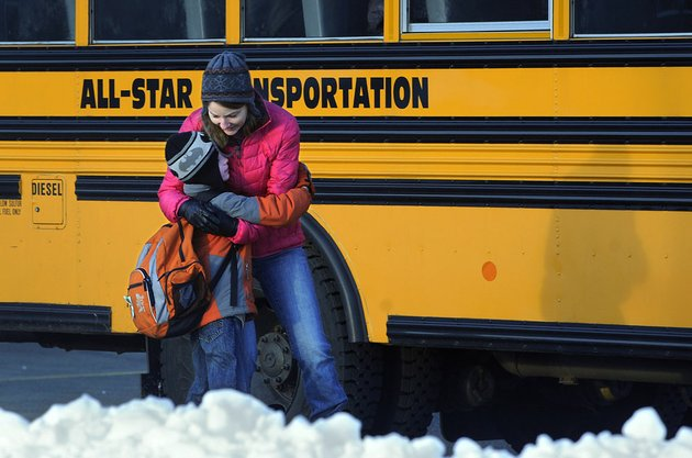 a-woman-hugs-a-child-before-he-boards-a-bus-on-the-first-day-of-classes-after-the-holiday-break-in-newtown-conn-on-wednesday-jan-2-2013-children-from-sandy-hook-elementary-school-returned-to-school-thursday-in-the-neighboring-town-of-monroe