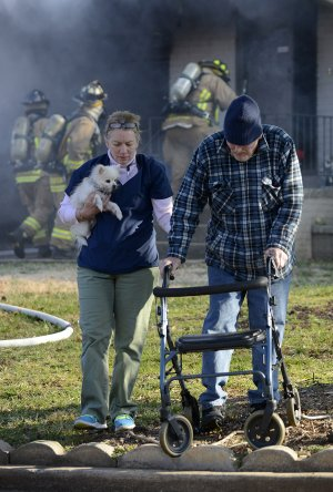 "Kim Benham, left, leads John Logston and his dog ""Tuffy"" away from his home Thursday as Bentonville firefighters work to contain a fire that broke out in the garage of Logston's home at 308 Magnolia Drive in Bentonville. Logston and wife Charleta were uninjured in the fire. Benham, a home health care nurse, alerted the Logstons to the fire when she arrived at the home and discovered smoke coming from the garage.