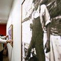 Chris Engholm of Bentonville hangs a piece of art on the wall Thursday at the Arts Center of the Oza...