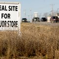 Motorists pass along West Walnut Street on Friday in Rogers past a sign promoting property for sale ...