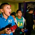 Salvador Aguilar, 10, left, of Avoca and Cesar Nava, 8, of Rogers play a video game Friday at the Bo...
