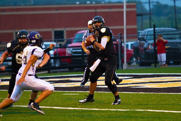 #4 QB Ty Storey looks down field as a Ozark defender pressures him.