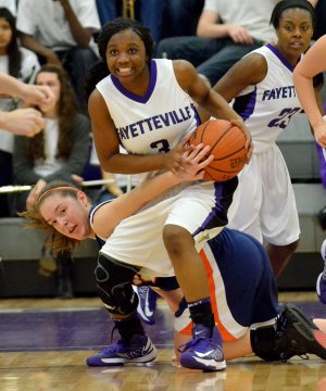 Jaylah Prude, Fayetteville guard, fights for control of the ball Friday against Rogers Heritage guard Brittany Ward at Bulldog Arena in Fayetteville.