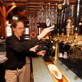 Maureen Robertson, a 10-year employee at Hog Haus, fills one of the restaurant and brewery's growler...