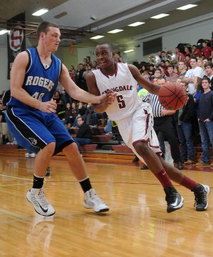 Tereke Eckwood, right, of Springdale High tries to get past Rogers High's Brett Gent on Jan. 4 in Springdale.