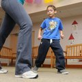 Luis Cruz, 7, watches Taylor Mills, Zumba instructor and children's services assistant, while dancin...