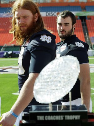 Notre Dame players Conor Hanratty and Tony Springmann eye The Coaches' Trophy during media day Saturday in Miami.