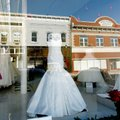 Downtown businesses are reflected in the storefront windows Friday of White Dress Boutique. Owner La...