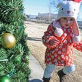 Kate Pendergraft, 17 months, runs around the Christmas tree Sunday at Frisco Station Park in downtow...